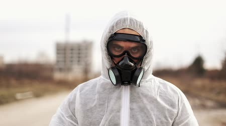 zehirli : Virologist man in protective costume and respirator gas mask walk in a deserted city at the industrial factory background