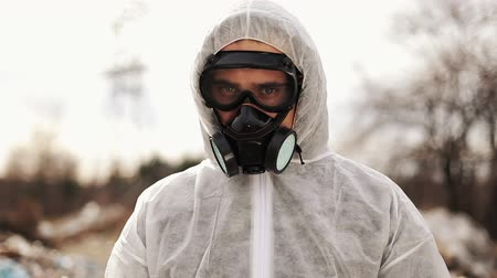 protective suit : Virologist Man in Protective Costume and Respirator Gas Mask Looking in Camera on in Landfill Site Pollution, Ecological Disaster