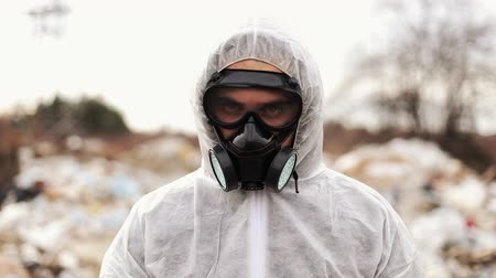 Virologist Man in Protective Costume and Respirator Gas Mask Looking in Camera on in Landfill Site Pollution, Ecological Disaster
