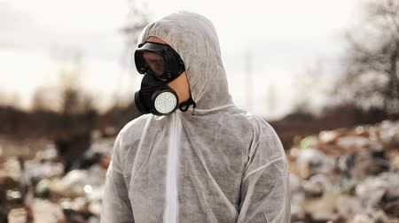 defunto : Virologist Man in Protective Costume and Respirator Gas Mask Camminando vicino a inquinamento del sito di discarica, disastro ecologico