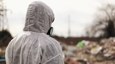 Virologist Man in Protective Costume and Respirator Gas Mask Walking near Landfill Site Pollution, Ecological Disaster