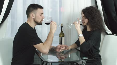 Man and woman drink wine sitting before the window