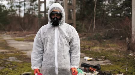 mustár : Man in bio-hazard suit and gas masks stands behind the stripe on the territory full of waste