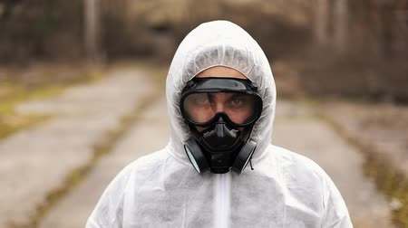 mustár : Man in bio-hazard suit and gas mask looks straight into the camera