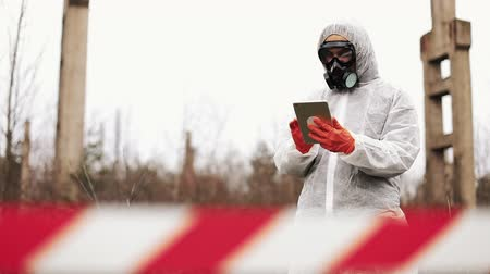 mustard : Man in bio-hazard suit and gas mask takes notes in his tablet standing on the polluted land