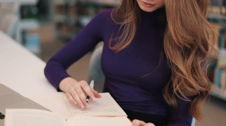 Girl writes down something from a book sitting at the table in a library