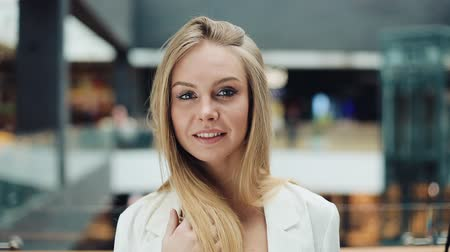 Smiling young blonde woman looks charming fixing her hair for a camera Stok Video