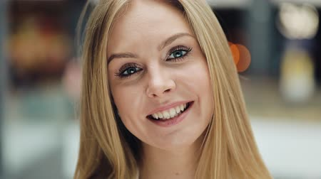 Smiling young blonde woman looks charming fixing her hair for a camera Стоковые видеозаписи