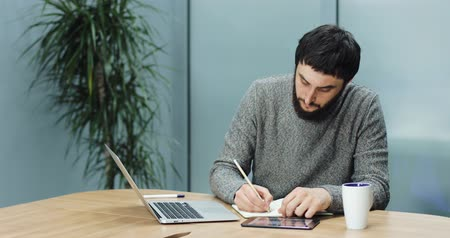 művelt : Man takes notes from his laptop to his laptop