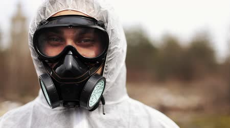 Man in bio-hazard suit and gas mask looks straight into the camera