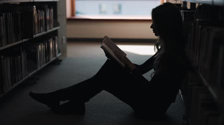 Girl sits on the floor and reads a book in the library