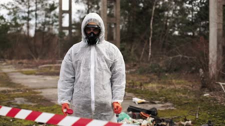 Man in bio-hazard suit and gas masks stands behind the stripe on the territory full of waste