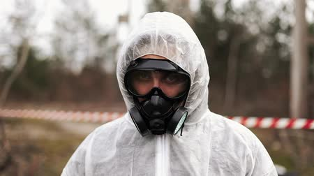 Man in bio-hazard suit and gas mask walks and looks straight into the camera