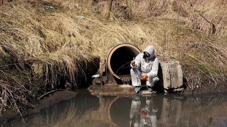Man in bio-hazard suit and gas mask checks the pollution of the water outside