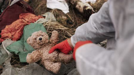 protective suit : Lost toys, waste and rubber on the ground in the forest