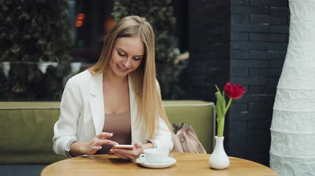 Charming blonde woman reads something in her smartphone sitting at the table in cafe Dostupné videozáznamy