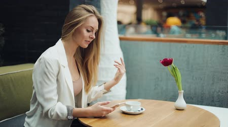 Charming blonde woman reads something in her smartphone sitting at the table in cafe Стоковые видеозаписи