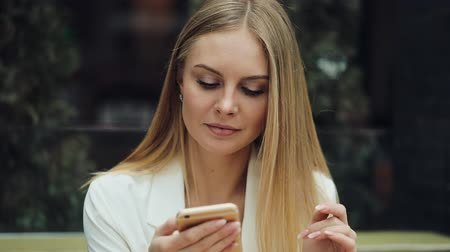 Charming blonde woman reads something in her smartphone sitting at the table in cafe Stok Video