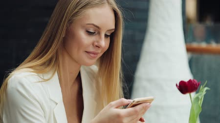 Charming blonde woman reads something in her smartphone sitting at the table in cafe Stock Footage