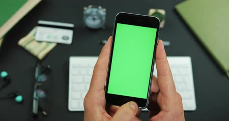 Man holds smartphone with green screen over a working table and taps something on it Stok Video