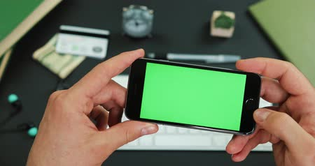 Man holds smartphone with green screen over a working table and taps something on it Stock Footage