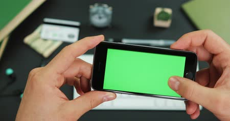 vertical : Man holds smartphone with green screen over a working table and scrolls something on it