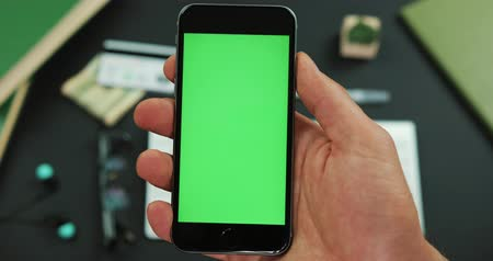 hitel : Man holds a black smartphone with green screen over a working table