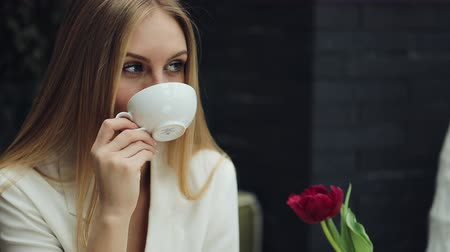 imbibe : Adorable young woman drinks her coffee sitting in the cafe