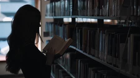 Silhouette of a girl looking at the books before a shelf in the library Стоковые видеозаписи