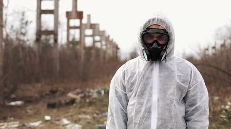 Man in bio-hazard suit and gas mask stands before the factory Стоковые видеозаписи