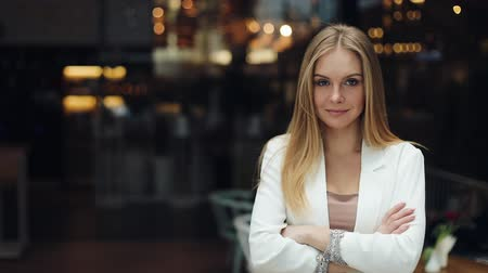 Attractive blonde woman looks straight into the camera and crosses her hands standing in the shopping mall