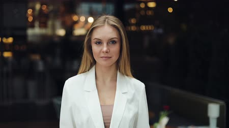 Attractive blonde woman looks straight into the camera standing in the shopping mall