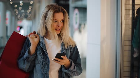 Smiling blonde girl reads something in her phone walking with shopping bags around a shopping mall