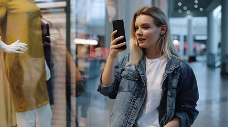 Girl talks on the phone and films a video on her smartphone standing before a show window in a shopping mall