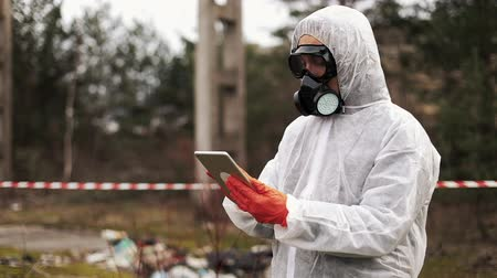 Man in bio-hazard suit and gas mask takes notes in his tablet standing on the polluted land