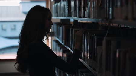 művelt : Silhouette of a girl looking at the books before a shelf in the library Stock mozgókép