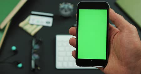 keying : Man holds a black smartphone with green screen over a working table