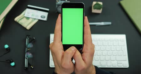 Man holds a black smartphone with green screen over a working table and scrolls something on it Стоковые видеозаписи
