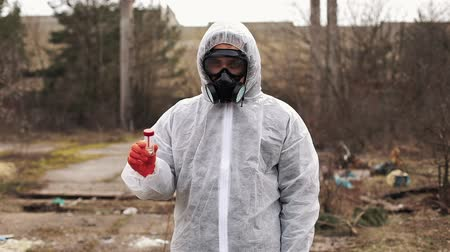 protective suit : Man in bio-hazard suit and gas mask stands before the factory Stock Footage