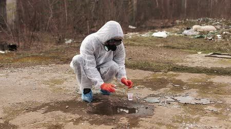 veneno : Man in bio-hazard suit and gas masks takes water and ground for the analysis