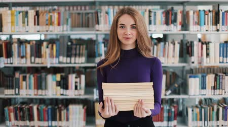 akademický : Smiling female student hold books walking before the shelves in the library