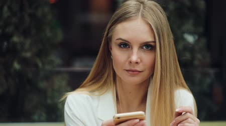 botok : Charming blonde woman reads something in her smartphone sitting at the table in cafe Stock mozgókép