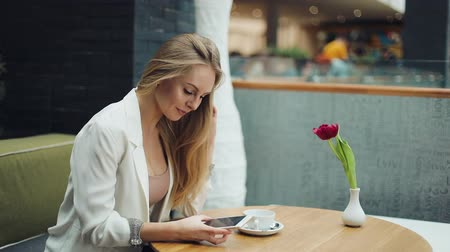 tebliğ : Charming blonde woman reads something in her smartphone sitting at the table in cafe Stok Video