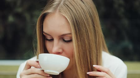 Adorable young woman drinks her coffee sitting in the cafe
