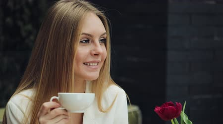 портфель : Adorable young woman drinks her coffee sitting in the cafe