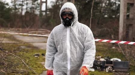 Man in bio-hazard suit and gas mask walks to the stipe on the land full of waste