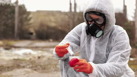 Man in bio-hazard suit and gas masks takes water and ground for the analysis