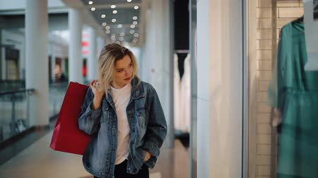 Thoughtful young blonde woman walks along a show window with bags in the shopping mall