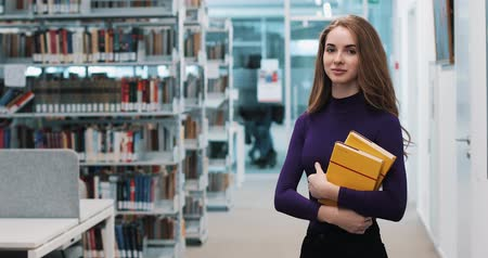 alluring : UKRAINE, LVIV - MARCH 26, 2018: Girl with long hair smiles standing before the shelves in the library Stock Footage