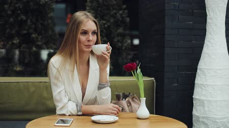 Young blonde woman takes a cup of coffee to her lips sitting at the table in cafe
